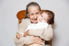 Сute gray-haired grandmother with gold teeth in knitted sweater hugs granddaughter with chicken pox, white dots, blisters on face stock image