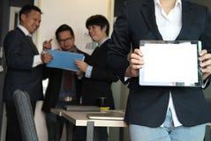 Таблетка владением коммерсантки на рабочем месте выставки молодой женщины сообщают Стоковая Фотография