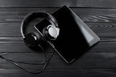 Таблетка и наушники цифров на темном деревянном столе Стоковое Фото