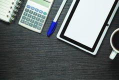 Таблетка, калькулятор, ручка, кофе и блокнот цифров на темной древесине Стоковые Изображения RF