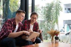 Таблетка & кредитная карточка пользы человека & женщины для онлайн покупок Молодые Стоковое Изображение