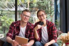 Таблетка & кредитная карточка пользы человека & женщины для онлайн покупок Молодые Стоковое Изображение RF