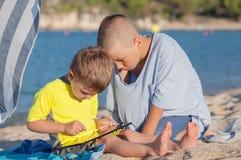 Таблетка пляжа детей Стоковые Изображения