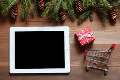 Таблетка с подарком и малой магазинной тележкаой на деревянном столе Стоковая Фотография