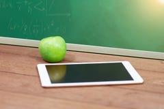 Таблетка цифров и зеленое яблоко на столе Стоковое фото RF