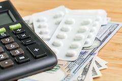 Таблетки в белом пакете на куче денег банкнот доллара США с концепцией калькулятора, здравоохранения, медицинских или фармации це стоковое изображение