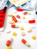 Таблетки лекарства белые и красочные на белой предпосылке стоковое изображение