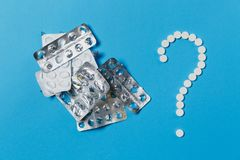 Таблетки лекарства на предпосылке цвета Концепция здоровья, обработки, выбора, здорового образа жизни стоковая фотография