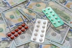 Таблетки на деньгах 100 долларов Расходы медицины Высокие цены дорогой принципиальной схемы лекарства стоковая фотография