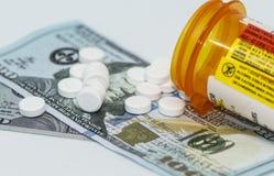Таблетки Oxycodone на 100 долларовых банкнотах стоковое изображение rf