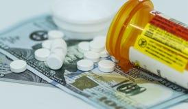 Таблетки Oxycodone разливая на 100 долларовых банкнот стоковые фотографии rf