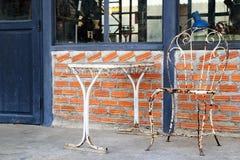 Таблица винтажного металла белая с стулом на предпосылке кирпичной стены и голубых деревянных дверей Стоковое фото RF