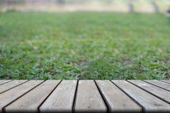 Таблица деревянной доски пустая перед запачканным backgro зеленой травы Стоковые Фотографии RF