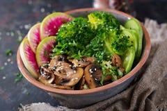 Таблица еды обедающего шара Будды Vegan Здоровый шар обеда vegan Зажаренные грибы, брокколи, салат редиски Стоковые Изображения RF