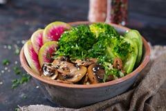 Таблица еды обедающего шара Будды Vegan Здоровый шар обеда vegan Зажаренные грибы, брокколи, салат редиски Стоковое Изображение RF