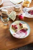 Таблица закуски с салями, сырами, яблоком, виноградинами на деревянном кухонном столе с доской Стоковые Изображения RF