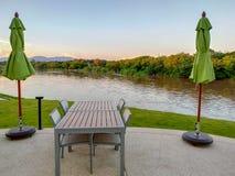 Таблица и стулья помещенные в отдыхать Реки и горы взгляда в вечере стоковое фото