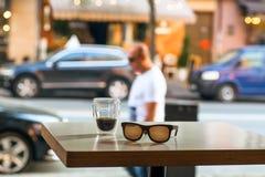 Таблица кафа улицы с стеклом кофе и пустым местом выходя посетителя Большая концепция места города Стоковое Изображение