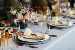Таблица, который служат для специального случая Пустые плита, стекла, вилки, салфетка и цветки на таблице предусматриванной с бел стоковые фотографии rf