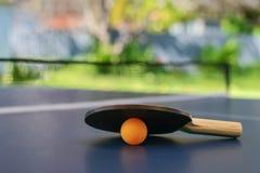 Таблица настольного тенниса с шариком ракетки и апельсина на задворк Стоковые Изображения