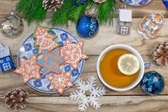 Таблица Нового Года с ветвями и украшениями ели на деревянной предпосылке Чай с печеньями, пряник рождества, небольшие звезды стоковые изображения