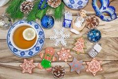 Таблица Нового Года с елевыми ветвями и украшениями Чай с печеньями, пряник рождества, небольшие звезды предпосылка праздничная стоковое изображение rf