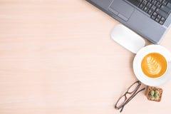 Таблица офиса с компьтер-книжкой, мышью, кофейной чашкой на предпосылке таблицы Стоковое Изображение RF
