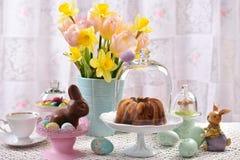 Таблица пасхи праздничная с мраморным тортом кольца под стеклянным куполом Стоковое Изображение