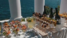 Таблица приема с рюмками fillled со свежим салатом Панорама фокуса таблицы служила outdoors около моря видеоматериал