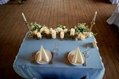 Таблица свадьбы сервировки Накрахмаленные белые салфетки, приведенные свеча и цветки на голубой скатерти Таблица новобрачных Стоковые Изображения RF