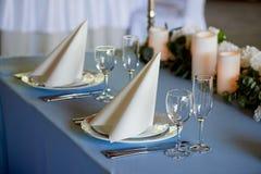 Таблица свадьбы сервировки Накрахмаленные белые салфетки, приведенные свеча и цветки на голубой скатерти Таблица новобрачных Стоковое Изображение
