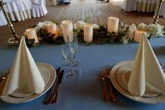 Таблица свадьбы сервировки Накрахмаленные белые салфетки, приведенные свеча и цветки на голубой скатерти Таблица новобрачных Стоковая Фотография RF