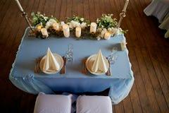 Таблица свадьбы сервировки Накрахмаленные белые салфетки, приведенные свеча и цветки на голубой скатерти Таблица новобрачных Стоковые Фото