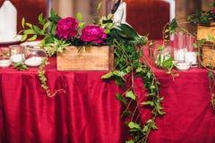 Таблица свадьбы украшена с пионами, хворостинами плюща и свечами Стиль деревенский стоковое изображение