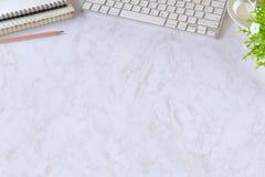 Таблица стола офиса белая с портативным компьютером, поставками и кружкой кофе Место для работы взгляд сверху и космос экземпляра Стоковое Фото