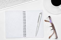 Таблица стола офиса с тетрадью, eyeglasses, кофейной чашкой и keyb Стоковое фото RF