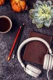 Таблица с блокнотом, наушниками и кофе Стоковая Фотография