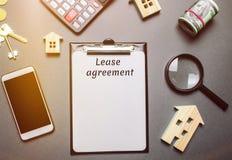 Таблица с деревянными домами сбывание ренты домов квартир имущества реальное Арендный договор контракт между арендодателем и less стоковое изображение