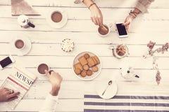 Таблица с кофе, газетой, мобильным телефоном, человеком и женщиной Стоковая Фотография RF