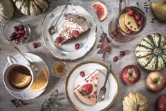 Таблица с нагрузками чая, тортов, пирожных, десертов, плодов, цветков и старых ложек и груши, яблок и тыкв стоковое изображение