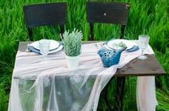 Таблица украшения свадьбы в деревенском стиле на зеленой траве Закройте вверх темной скатерти деревянного стола, белых, блюд и кр Стоковые Фото