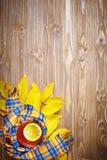 Таблица, украшенная с листьями осени, ягодами и свежим чаем Осень крупный план предпосылки осени красит красный цвет листьев плющ Стоковое Изображение