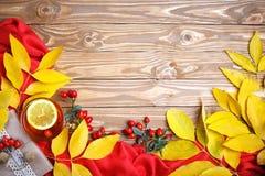 Таблица, украшенная с листьями осени, ягодами и свежим чаем Осень крупный план предпосылки осени красит красный цвет листьев плющ Стоковое фото RF