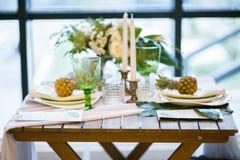 Таблица украшенная с цветом плит, ананасов, свечей и цветков, зеленых и белых Стоковые Изображения RF