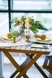 Таблица украшенная с цветом плит, ананасов, свечей и цветков, зеленых и белых Стоковые Фото