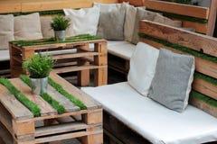 Таблицы и софы деревянных паллета и травы Стоковое фото RF
