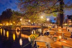 Таблицы кафа Amterdam, канал, мост и средневековые дома в e Стоковое Изображение