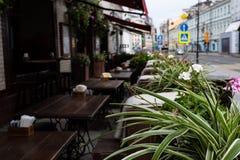 Таблицы улицы вне кафа на заднем плане defocused на переднем плане, листья цветков стоковые изображения rf