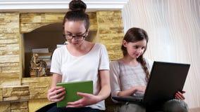 Таблетка девочка-подростка изменяя белая для зеленой книги, детей тратя время совместно около камина акции видеоматериалы