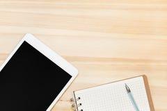 Таблетка и бумага цифров на деревянном столе Стоковая Фотография RF